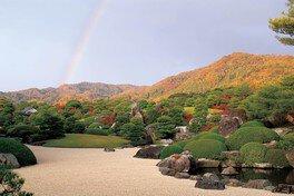 借景の山々が紅葉し自然との調和が美しい秋の枯山水庭